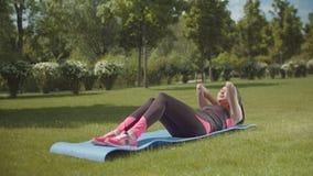 Sitzfrauen-Trainings-ABS auf Sportmatte im Stadtpark stock video footage