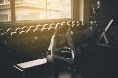 Sitzfrauensitzen und nach der Schulungseinheit in der Turnhalle, Frau sich entspannen, die einen Bruch nach Übung und Training, K stockfotos