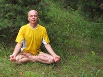Sitzmann im Gelb in der Meditation Stockfoto