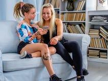 Sitzt blonde Frau zwei auf einer Couch und mit Smartphone Lizenzfreie Stockfotografie