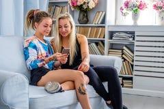 Sitzt blonde Frau zwei auf einer Couch und mit Smartphone Lizenzfreie Stockfotos