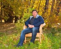 Sitzt die Entspannung des Mannes in einem geflochtenen Stuhl Stockbild