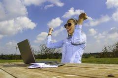 Sitzt die Frauen, die vom Haus arbeiten, im Garten mit einem Laptop und ihr, die wegen eines erfolgreichen Abkommens glücklich si Stockfoto