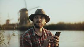 sitzt erfolgreicher kaukasischer Mann 4K nahe Sonnenuntergangsee Landwirtschaft des Geschäftsmannes in einem Hut unter Verwendung stock video footage