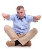 Sitzt zufällige Mitte gealterter Mann mit den Daumen unten Stockbild