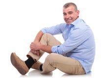 Sitzt zufällige Mitte gealterter Mann und lächelt an Ihnen Lizenzfreie Stockfotos