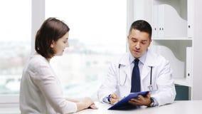 Sitzung lächelnden Doktors und der jungen Frau am Krankenhaus stock footage