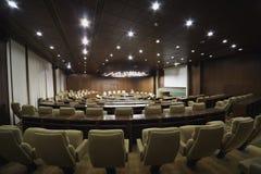 Sitzungssaal mit runder Tabelle und Lehnsesseln um sie Stockfotos