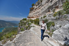 Siurana's cliff of Catalonia in spring. The woman is walking along the rocky pass on the abrupt cliff. There are a river and the overgrown mountains in the Stock Photos