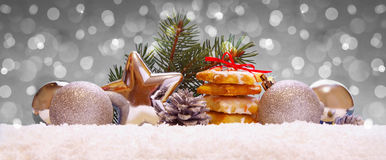 Siver balls and christmas cookies on snow . stock photo