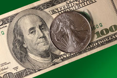 Siver coin and dollar over a green background Stock Images