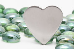 Siver Heart. Silver metal heart against a background on small green glass stones Royalty Free Stock Images