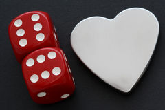 Siver Heart with Dice. Silver hearts on black background next to two dice showing double six Royalty Free Stock Photo
