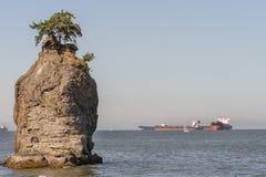Siwash Rock with huge waiting sea vessels.