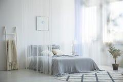 Siwieje dzianiny koc umieszczającą na łóżku z baldachimem w białym hotelu r zdjęcie stock