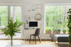 Siwieje krzesła przy biurkiem z komputerem stacjonarnym w scandi otwartej przestrzeni wewnątrz zdjęcia royalty free