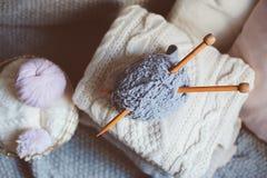 Siwieje przędzy piłkę z dziewiarskimi igłami w kruszcowym koszu z trykotowymi pulowerami na tle i różowi Zdjęcia Stock