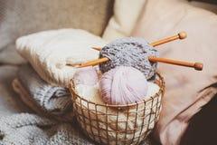 Siwieje przędzy piłkę z dziewiarskimi igłami w kruszcowym koszu z trykotowymi pulowerami na tle i różowi Zdjęcie Royalty Free