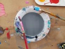 Siwieje wodę w naczyniu z farb muśnięciami Fotografia Royalty Free