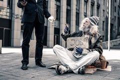 Siwowłosy starszy bezdomny przewożenia nameplate i brać kąska jedzenie fotografia royalty free