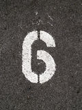 Six. A close up on white stenciled number six on black pavement Royalty Free Stock Photo