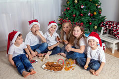 Six adorable children, having fun in front of the Christmas tree Royalty Free Stock Images