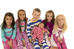 Six adorable children wearing Christmas pajamas smiling happy Stock Photo