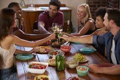 Six amis faisant un pain grillé à un dîner, vue élevée Image stock