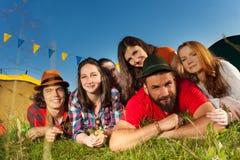 Six amis heureux ayant le repos au camping en été Images stock