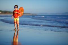 Six années de garçon avec le swimtrainer sur la plage exotique Image stock