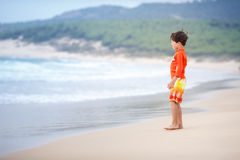 Six années de garçon jouant sur la plage exotique Photo libre de droits