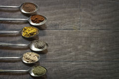 Six Antique Silver Spoons with Different Spices in royalty free stock images