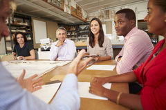 Six Architects Sitting Around Table Having Meeting. Discussion Designs On Table Royalty Free Stock Photo