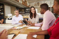Six Architects Sitting Around Table Having Meeting. Using Digital Tablet Stock Image
