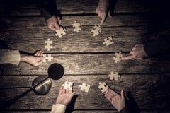Six associés plaçant le puzzle rapièce en cercle images libres de droits