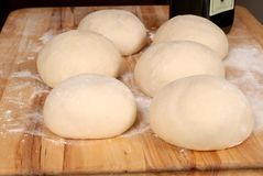 Six balls of freshly made pizza dough on cutting board Stock Photography