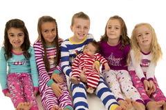 Six beautiful children wearing their winter pajamas sitting. Six beautiful children wearing winter pajamas sitting royalty free stock photography