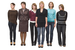 Six beautiful girls in line. Six beautiful models a women stand on white background in studio. Full-length portrait. One of them is smiling Royalty Free Stock Image