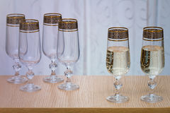 Six beautiful glass wine glasses, two filled with champagne. Stock Photos