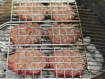 Six beef burgers grilled. Six beef burgers being prepared in a grill rack royalty free stock image