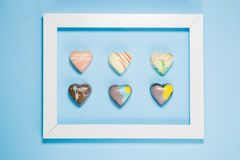 Six Belgian chocolate hearts framed on blue background Royalty Free Stock Images