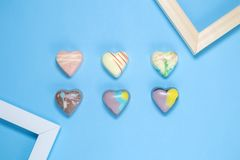 Six Belgian chocolate hearts with frames on blue background Stock Photo