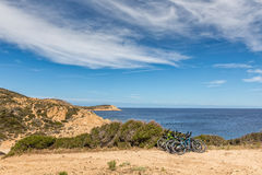 Six bicycles resting on bush on coastal path in Corsica Stock Photography
