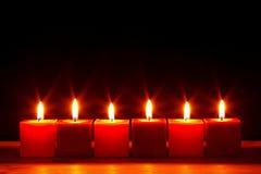 Six bougies carrées brûlant de lumineux Images stock