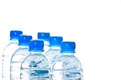 Six bouteilles d'eau minérales d'isolement sur le blanc Photographie stock libre de droits