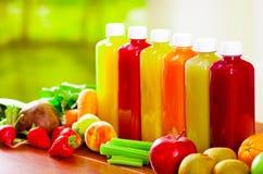 Six bouteilles de jus organique délicieux se tenant dans une rangée sorrounded par des fruits et des veggies, belles couleurs Images libres de droits