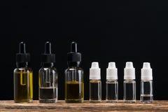 Six bouteilles de liquides sont arrangées sous forme de fond sur la table photographie stock libre de droits
