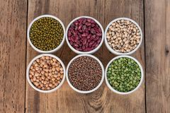 Six bowls with cereals in two lines on wooden desk. Six bowls with cereals (bean pea lentil, haricot, kidney)  on wooden desk Stock Photography