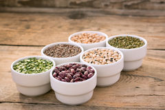 Six bowls with cereals on wooden desk. Six bowls with cereals (bean,  pea, lentil, haricot, kidney)  on wooden desk Stock Photos