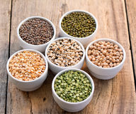 Six bowls with cereals on wooden desk. Six bowls with cereals (bean  pea lentil, haricot, kidney) on wooden desk set in a circular Stock Photography
